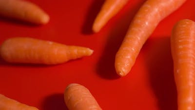 Tasty Orange Carrots on a Red Background
