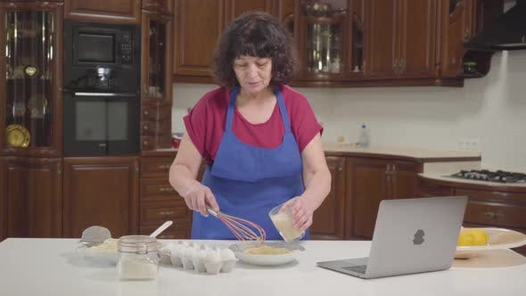 Thumbnail for Senior Caucasian Woman Checking Recipe Online and Mixing Milk Into Dough