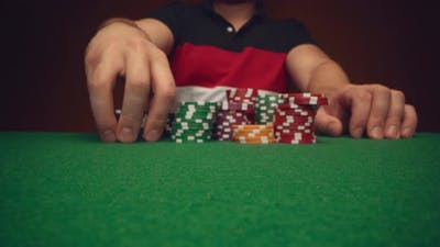 Male Player Moving Casino Chips on Poker Table Close Up