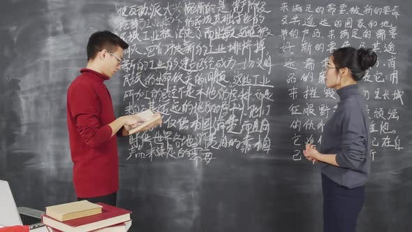 Female Student Answering at Blackboard during Lesson