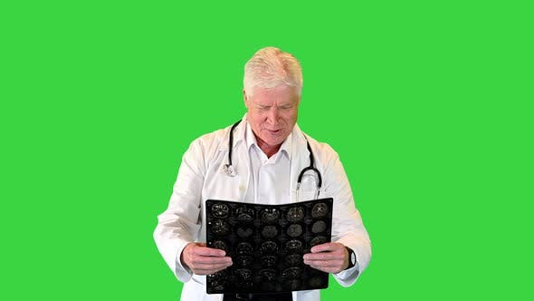 Doctor in a Rush Viewing MRI Scans While Walking on a Green Screen Chroma Key