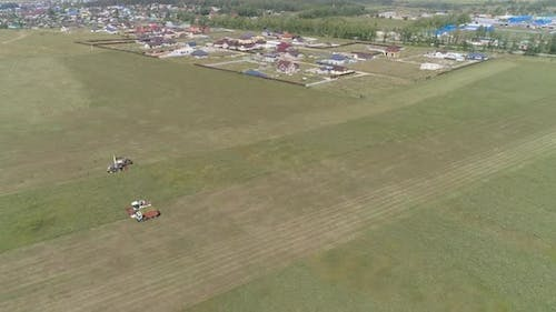 Aerial view of Combine harvesting and truck on grass field. 20