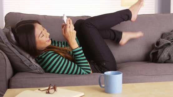 Thumbnail for Japanese woman happily texting and laughing on couch