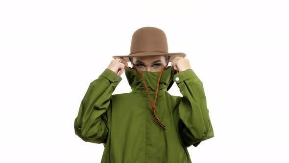 Frau in einem Herbstlook im Studio im grünen Parka und Hut dreht und Posen zur Kamera