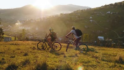 Family Couple of Cyclists Riding in the Mountains