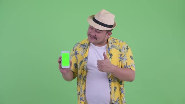 Cover Image for Happy Young Overweight Asian Tourist Man Showing Phone and Giving Thumbs Up