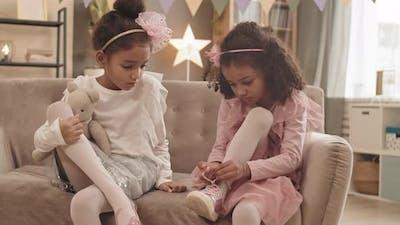 Sister Watching Girl Lacing Shoe