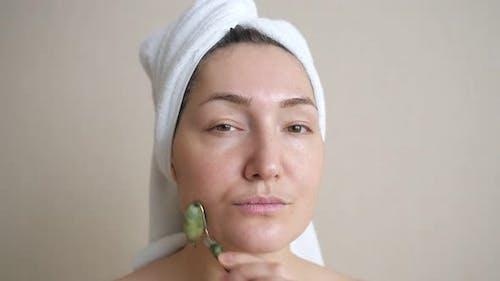 Closeup of Woman Doing Facial Massage with Jade Roller