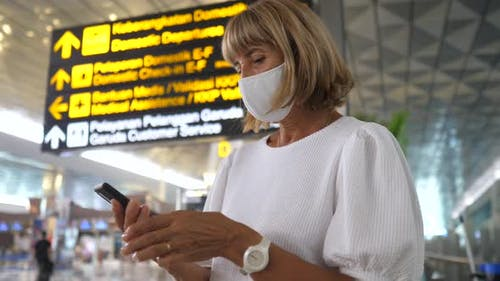 Woman in a Face Mask Checking Her Phone Before the Departure at the Airport
