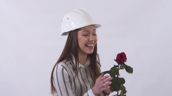Cover Image for Joyful Beautiful Woman in White Helmet Holding a Red Rose in Her Hands and Very Happy Isolated on