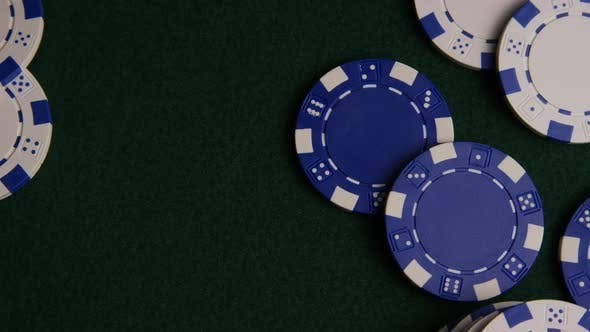 Rotating shot of poker cards and poker chips on a green felt surface - POKER 021