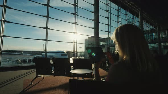 Thumbnail for The Passenger Uses the Tablet in the Terminal of the Airport, the Window Shows a Flying Airliner