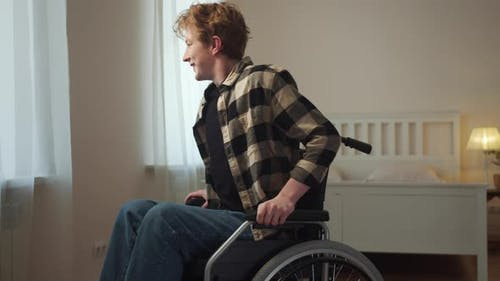 A Disabled Man is Riding on the Wheelchair Through the Room