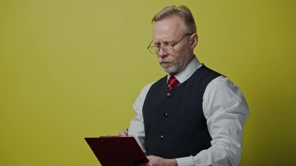 Thumbnail for Portrait of serious grey haired man with a folder