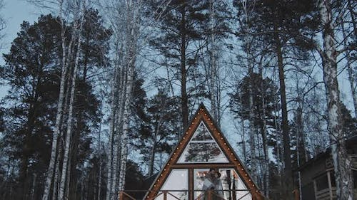 Couple Standing on Porch of Cabin on Cold Day