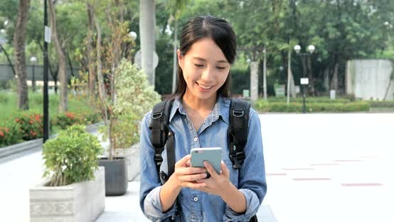 Thumbnail for Woman sending sms on cellphone in the city park