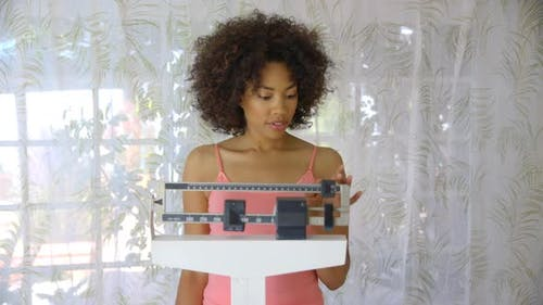 Young woman recording weight loss on scale