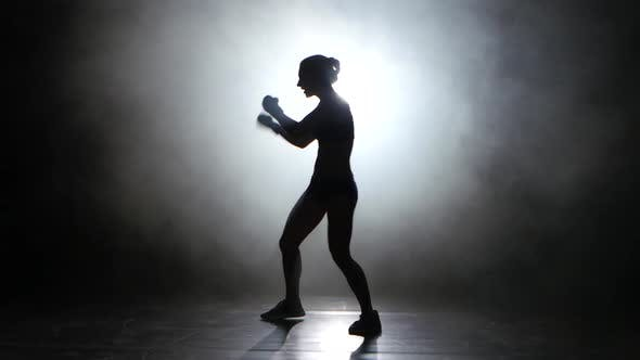 Thumbnail for Champion Boxer Sends the Punches. Silhouette. Light From Behind. Black Background. Side View