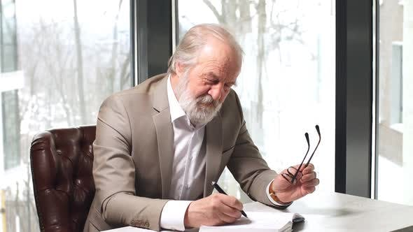 Thumbnail for Old Professor with Grey Hair and Beard in Beautiful Suit Taking Notes in the Notebook