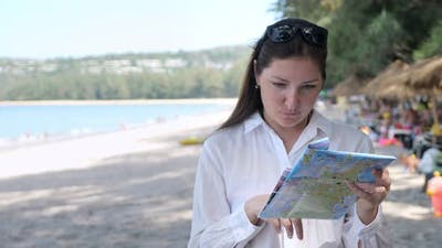 Young Woman in a White Shirt on the Beach Considers a Map