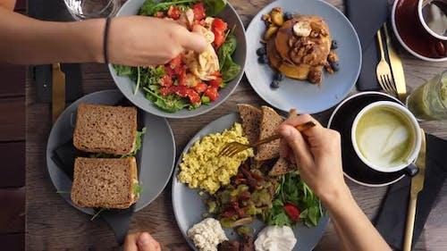 Top View of Hands Eating Healthy Organic Vegan Breakfast of Full English, Pasta Salad and Vegan
