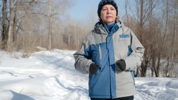 Thumbnail for Portrait of an adult woman running through the winter forest at daytime