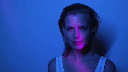 Beautiful Model in a Blue Dark Room Standing in Front of Wall with White Top