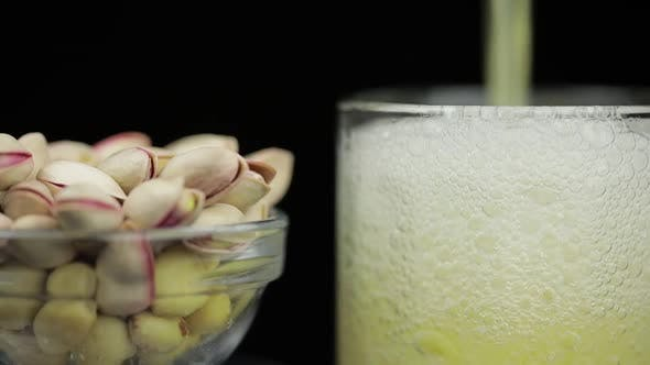 Thumbnail for Beer Is Pouring Into Glass on Black Background. Bowl of Pistachios Nuts