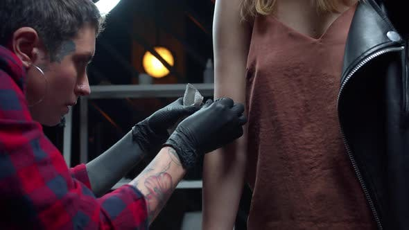 Girl Puts Temporary Tattoo on Arm of a Client