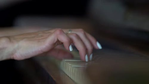 Close-up of a Woman's Hands with a White Manicure Playing the Piano Close-up.