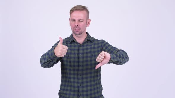 Thumbnail for Portrait of Happy Blonde Hipster Man Choosing Between Thumbs Up and Thumbs Down