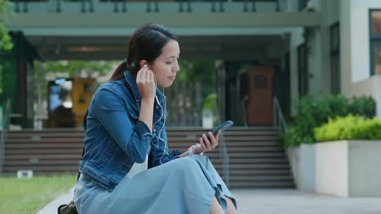 Cover Image for Woman listen to music on mobile phone