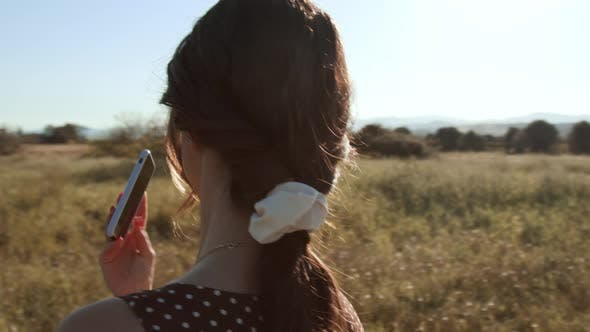 Young girl use a smartphone outdoors