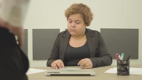 The Plump Woman Sitting at the Table in the Office