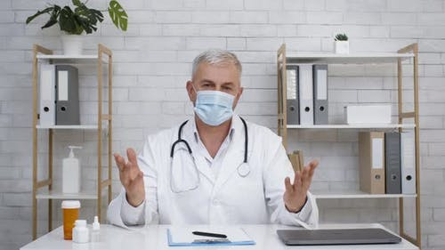 Doctor Wearing Face Mask Talking To Camera Sitting In Clinic