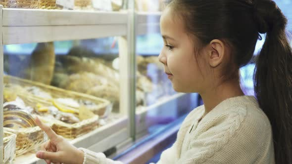 Thumbnail for Close Up Shot of a Pretty Little Girl Posinting at the Desserts at the Bakery