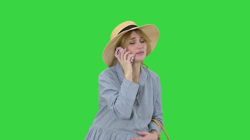 Worried Pregnant Woman Talking on the Phone Having Contractions on a Green Screen, Chroma Key.