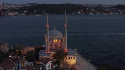 Ortakoy Mosque Illuminated in Beautiful Yellow Light on Water Side at Dusk with Bosphorus and Bridge