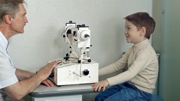 Thumbnail for Ophthalmologist in exam room with little boy sitting in