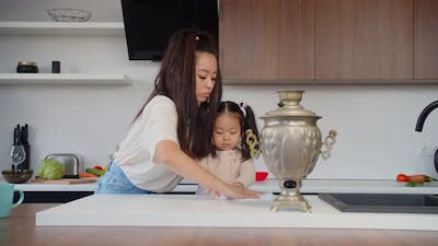 Asian Mom and Baby Daughter Cleaning Table in Kitchen