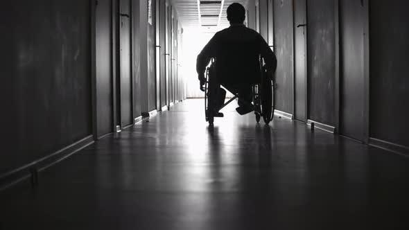 Thumbnail for Silhouette of Man Riding on Wheelchair along Corridor