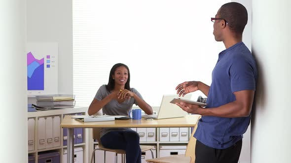 Thumbnail for African American business colleagues talking to each other in office