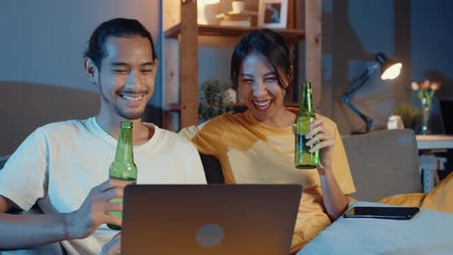 Happy young asian couple enjoy night party event online sit couch use laptop computer video call.