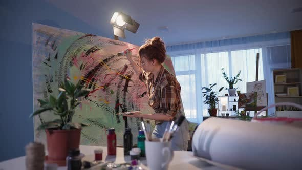 Young Stylish Female Artist with Dirty Hands in Paint Painting Picture on Large Canvas Girl