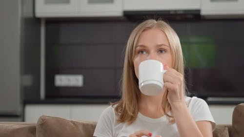 Adorable Woman Enjoying Hot Beverage While Watching Movie