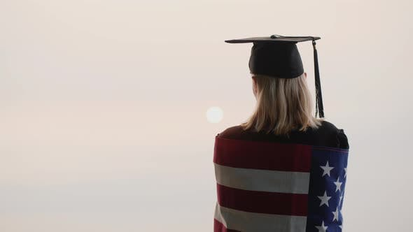 Thumbnail for Rear View of a Graduate with the Flag of USA