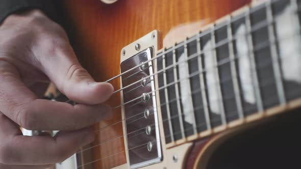 Fingerstyle guitar player practicing song on guitar. Hands picking and pulling guitar strings.