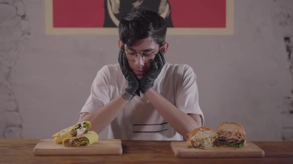 Thumbnail for Young Skinny Man in Glasses and Black Gloves Sitting at the Table in Front of Appetizing Burger