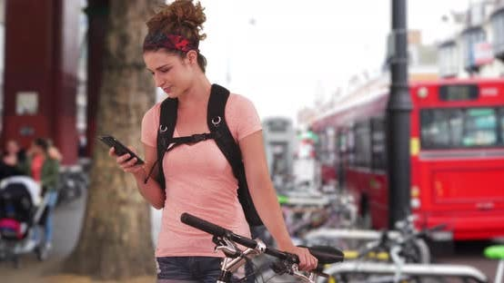 Thumbnail for Fit Caucasian female bicyclist sending text message in London street