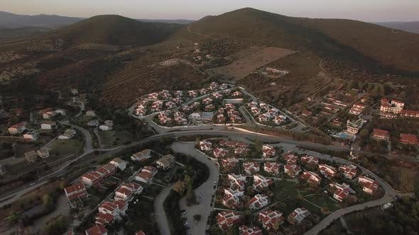 Thumbnail for Aerial Scene of Neighbourhood and Green Hills in Trikorfo Beach, Greece